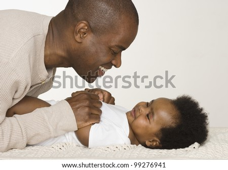 Father changing his baby daughter's diaper