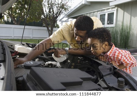 Father checking oil level with his little son