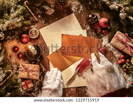Father Christmas writing a letter to celebrate Xmas in an overhead view of his hands holding envelopes above vintage paper and a feather quill pen surrounded by decorations and gift lit by candlelight #1229715919