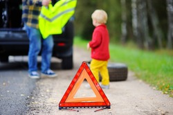 Father clothes yellow safety vest on his toddler son. Vehicle breakdown on travel trip