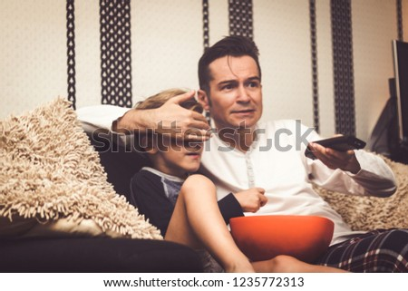 Father covering son's eyes and changing channel while watching inappropriate television content at home.