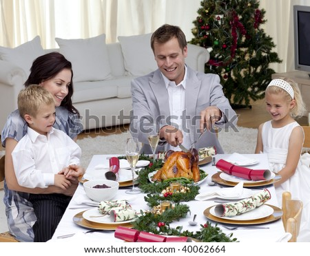 Father cutting a turkey in Christmas dinner for his family