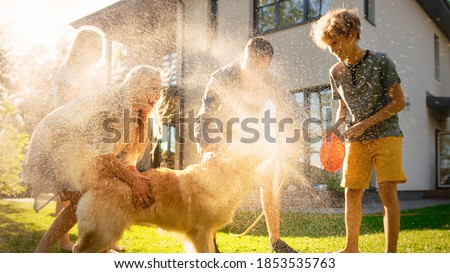 Father, Daughter, Son Play With Loyal Golden Retriever, Dog Tries to Catch Water from Garden Water Hose. Family Spending Fun Outdoors Time Together. Sunny Day Idyllic Suburban Home. Stock photo ©