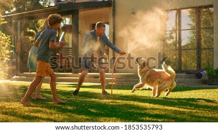 Father, Daughter, Son Play With Loyal Golden Retriever, Dog Tries to Catch Water from Garden Water Hose. Family Spending Fun Outdoors Time Together in Backyard. Golden Hour Sunset.