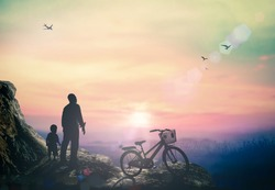 Father Day concept: Silhouette father and son standing with bicycle over sunset mountain background