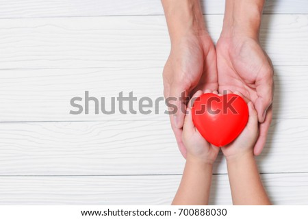 Father Day's and Mother's Day. Man holds his hands son supporting red heart. #700888030