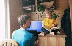 father developer freelancer work from home and help son child to read book, concept of self-isolated lifestyle workspace workplace, parenthood multitasking productivity in home office