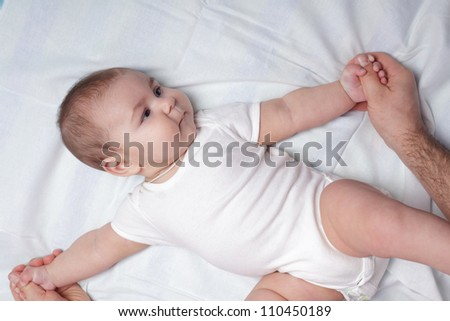 Father do everyday exercises and massaging with baby