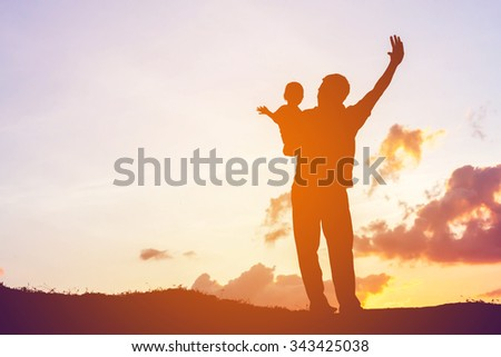 father encouraged her son outdoors at sunset, silhouette concept