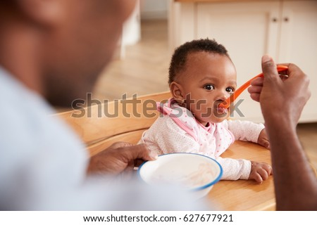 Father Feeding Baby Daughter In High Chair