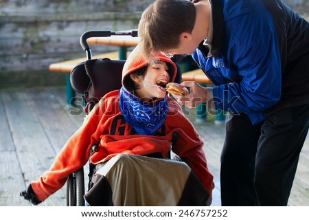 Father feeding disabled son a hamburger in wheelchair. Child has cerebral palsy Stock photo ©