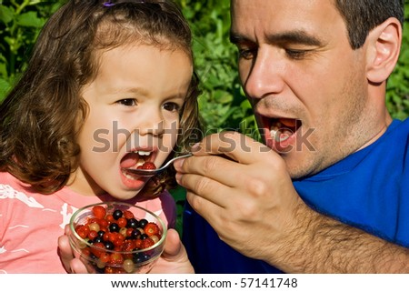 Father giving fresh fruits to his daughter