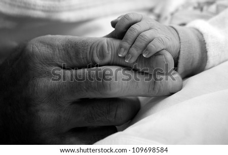 Father giving hand to a child closeup (black white)