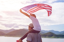 Father giving Happy piggyback ride to his cute son with a hand held American flag in standing in the summer sunshine. USA celebrate 4th of July- Independence Day.Patriotic holiday.