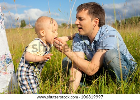 father giving his son wild strawberries on a summer field