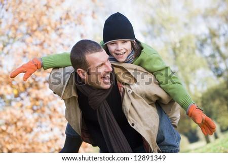 Father giving son piggyback through autumn woods