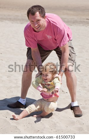 Father having fun with his daughter on the beach