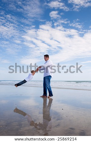 Father having fun with his son on a beach.