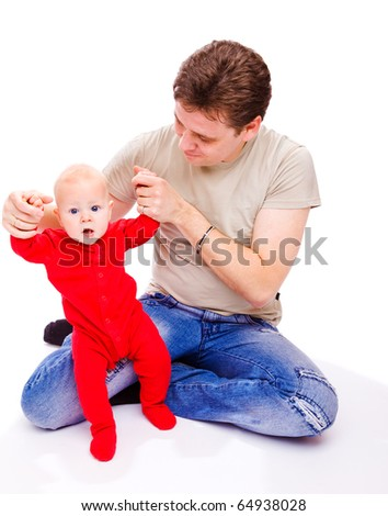 Father helping baby in red bodysuit to make his first steps