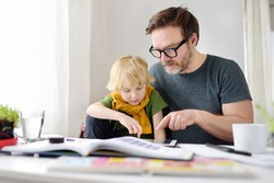 Father helping child do homework at home. Homeschooling, distance learning, online studying, remote education for kids during quarantine is a problems for many parents. Tutor teaching boy with ADHD.