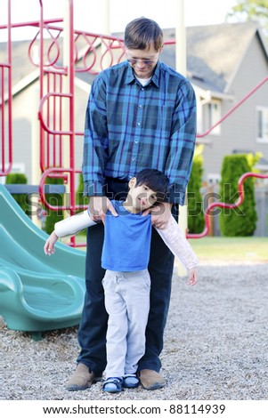 Father helping disabled four year old son to play at playground - stock photo