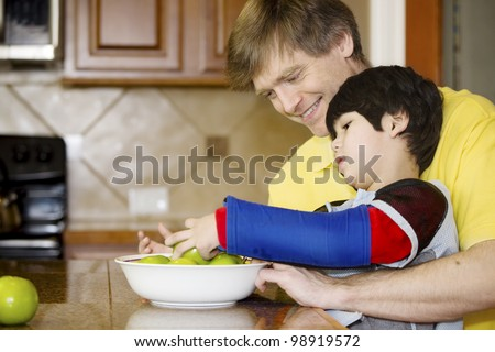 Father helping disabled son putting fruit into bowl in the kitchen. Son has cerebral palsy.