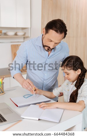Father helping his daughter to inscribe a circle #664484368