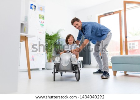 Photo of  Father helping his son to drive a toy peddle car