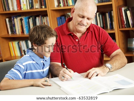 Father helping his young son do homework at the library.