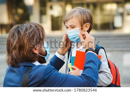 Father helping son and putting on face protective mask. Little boy going to school during coronavirus pandemic. Businessman father and son going to school. Schoolboy is ready go to school.