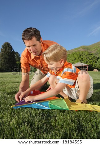 Father helping son build a kite outdoors
