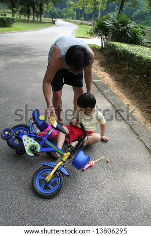 Father helping son getting up from falling off bicycle