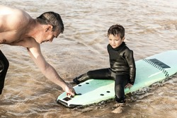 Father helping son surfing on board. High angle view of father helping little son in wetsuit sitting and swimming on surfboard on waves. Surfing concept