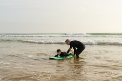 Father helping son swimming on surfboard. Middle aged father helping cute little son in wetsuit swimming on board on ocean waves. Surfing concept