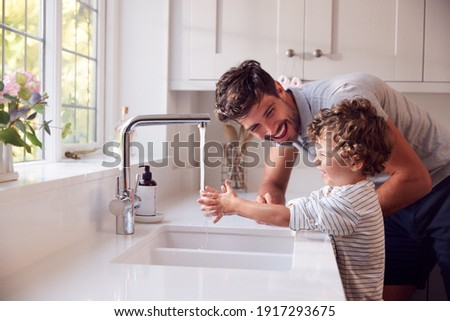 Father Helping Son To Wash Hands With Soap At Home To Stop Spread Of Infection In Health Pandemic
