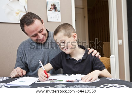 Father helping son with his homework sitting in at the table