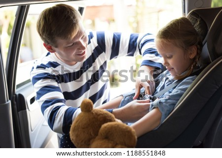 Father helping to put on the seat belt