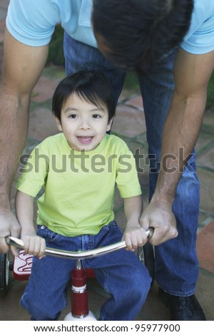 Father helping young son ride tricycle