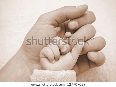 Father hold baby hand in the palm