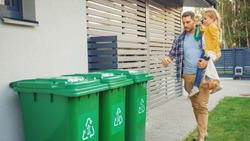 Father Holding a Young Girl and Going to Throw Away an Empty Bottle and Food Waste into the Trash. They Use Correct Garbage Bins Because This Family is Sorting Waste and Helping the Environment.