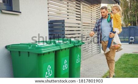 Father Holding a Young Girl and Going to Throw Away an Empty Bottle and Food Waste into the Trash. They Use Correct Garbage Bins Because This Family is Sorting Waste and Helping the Environment. Photo stock ©