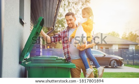 Father Holding a Young Girl and Throwing Away a Food Waste into the Trash. They Use Correct Garbage Bins Because This Family is Sorting Waste and Helping the Environment. Photo stock ©