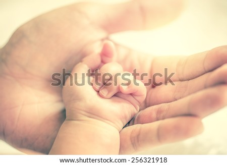 father holding baby hand in vintage filtered style
