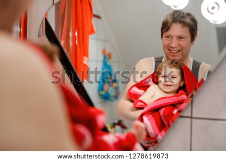 Father holding cute little toddler girl wrapped in towel after taking bath. Happy healthy baby child with wet hairs looking in mirror in bathroom and laughing. Family relationship of daughter and dad