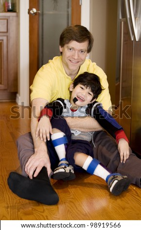 Father holding disabled son on kitchen floor. Son has cerebral palsy.