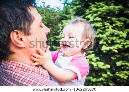 Father holding his laughing one-year-old daughter. Cute little baby girl shows her dad what to do to make her laugh. Happy Fathers Day concept image. Face portrait closeup on greenery background
