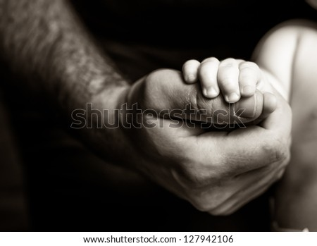 Father holding his son's hand - black and white photography