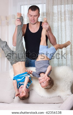 Father holding his two sons upside down.