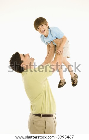 Father holding smiling son up overhead against white background.