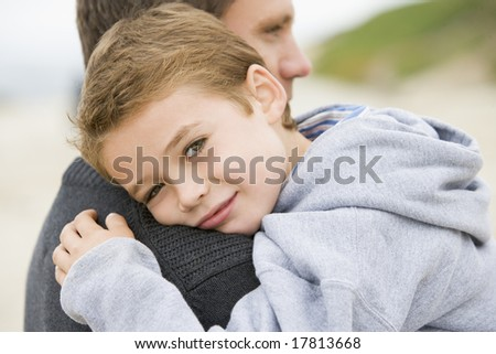 Father holding son at beach